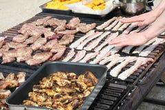 Mains de cuisinier tout en faisant cuire dans une grille géante d'un barbec extérieur photographie stock