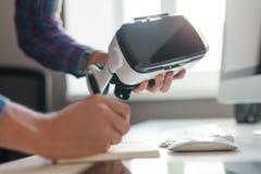 Mains de culture avec des lunettes de VR faisant des notes image stock