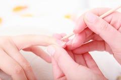 Mains de cuticles de nettoyage d'esthéticien avec le bâton cosmétique. Salon de station thermale de beauté image libre de droits