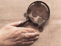 Mains de dame âgée, de loupe et d'argent Images stock