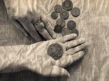 Mains de dame âgée, de loupe et d'argent Photographie stock