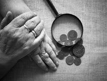 Mains de dame âgée, de loupe et d'argent Foyer mou sélectif Image libre de droits
