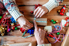 Mains de deux femmes enveloppant des cadeaux de Noël Images libres de droits