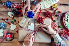 Mains de deux femmes enveloppant des cadeaux de Noël Photos stock