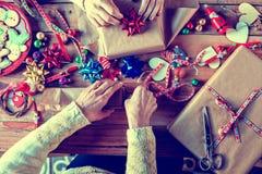 Mains de deux femmes enveloppant des cadeaux de Noël Photographie stock