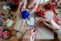 Mains de deux femmes enveloppant des cadeaux de Noël Images stock
