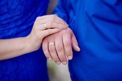 Mains de deux personnes affectueuses sur un fond bleu Images stock