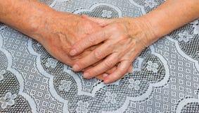 Mains de deux personnes supérieures affectueuses sur un fond de nappe Images libres de droits