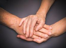Mains de deux personnes supérieures affectueuses sur un fond foncé Photos libres de droits