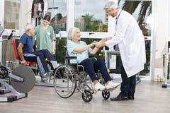 Mains de docteur Holding Senior Woman dans le fauteuil roulant Image stock