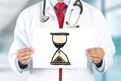 Mains de docteur tenant le signe avec l'horloge de sable Photo stock