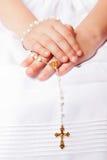 Mains de elle pendant le premier jour de communion Image stock