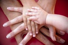 Mains de famille sur l'équipe Photo stock