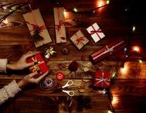 Mains de femelle préparant soigneusement beaucoup de cadeaux avec des lumières de Noël Photos libres de droits