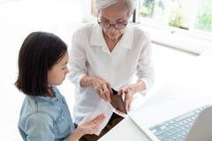 Mains de femme agée de plan rapproché portefeuille, grand-mère ou gardien ouverte donnant l'argent de poche à la petite-fille, un photos libres de droits