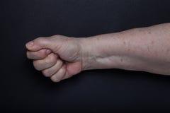 Mains de femme agée sur le fond noir Photos libres de droits
