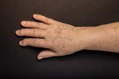 Mains de femme agée sur le fond noir toned Photo stock