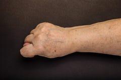 Mains de femme agée sur le fond noir toned Photographie stock libre de droits
