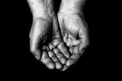 Mains de femme agée sur le fond noir toned Images stock