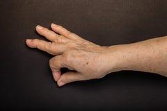Mains de femme agée sur le fond noir toned Images libres de droits