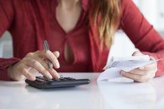 Mains de femme avec des factures sur la table Photos libres de droits