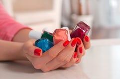 Mains de femme avec des vernis à ongles dans le salon d'ongle photographie stock libre de droits