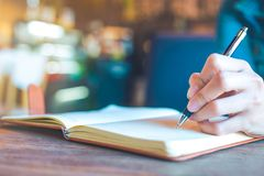 Mains de femme avec l'écriture de stylo sur le carnet dans le bureau Photographie stock