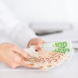 Mains de femme avec l'euro argent d'argent liquide Photographie stock libre de droits