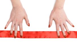 Mains de femme avec la bande rouge Photographie stock