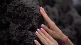 Mains de femme avec la manucure de couleur claire et le missanga gentil touchant la pierre noire banque de vidéos