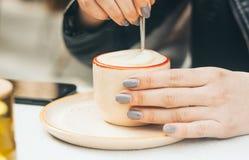 Mains de femme avec la manucure tenant une tasse avec le capuccino dehors photographie stock libre de droits