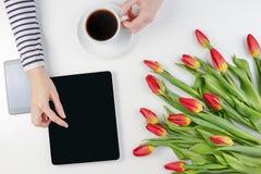 Mains de femme avec le comprimé d'ordinateur, la tasse de café, le téléphone portable et le beau groupe de fleurs sur la table bl Photos stock