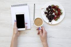 Mains de femme avec le smartphone, le latte, le carnet, les fraises et les cerises sur le fond en bois blanc, vue supérieure Photos stock