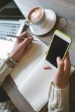 Mains de femme avec le stylo et le bloc-notes, tenant le smartphone avec le cof Photo libre de droits
