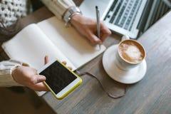 Mains de femme avec le stylo et le bloc-notes, tenant le smartphone avec le cof Image stock