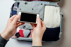 Mains de femme avec le téléphone sur le fond de la valise Open emballé photographie stock libre de droits