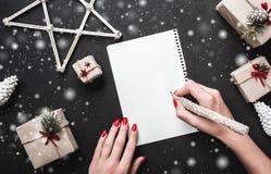 Mains de femme avec les clous rouges écrivant la lettre avec le stylo argenté Fond de Noël Images libres de droits