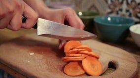 Mains de femme coupant en tranches la carotte sur la planche à découper banque de vidéos
