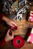 Mains de femme décorant des cadeaux et des décorations de Noël Images stock