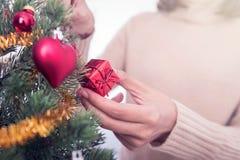 Mains de femme décorant l'arbre de Noël Photos stock