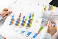Mains de femme d'affaires analysant des statistiques financières Image libre de droits