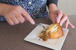 Mains de femme d'une cinquantaine d'années et de gâteau d'Apple et de noix Photographie stock