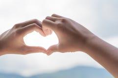 Mains de femme dans la forme du coeur d'amour Photos stock