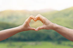 Mains de femme dans la forme du coeur d'amour Photo stock