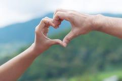 Mains de femme dans la forme du coeur d'amour Photographie stock libre de droits
