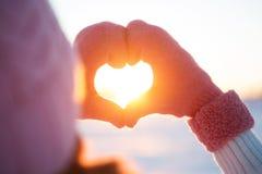 Mains de femme dans le symbole de coeur de gants d'hiver photographie stock