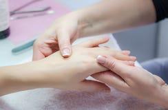 Mains de femme dans un salon de clou recevant un massage de main par un beaut Image stock