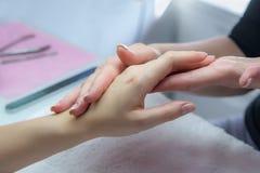 Mains de femme dans un salon de clou recevant un massage de main par un beaut Photographie stock libre de droits