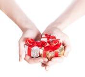 Mains de femme donnant des cadeaux d'isolement sur le blanc Images stock