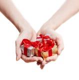 Mains de femme donnant des cadeaux d'isolement sur le blanc Photographie stock libre de droits